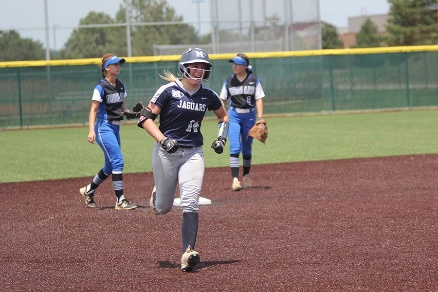After hitting a home run, senior Peyton Moeder smiles as she makes her way to home plate.