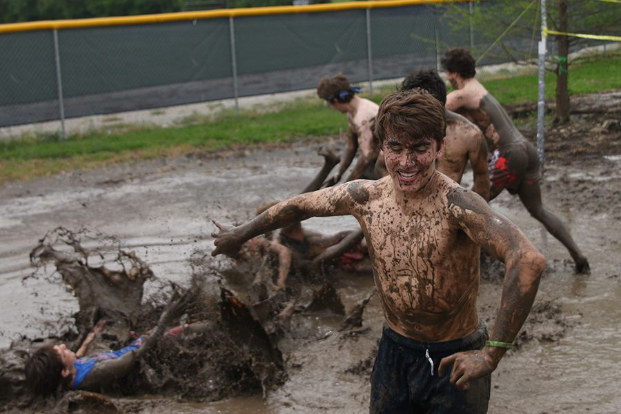 Running+away%2C+senior+Max+Whisler+smiles+as+his+friends+fall+in+the+mud.