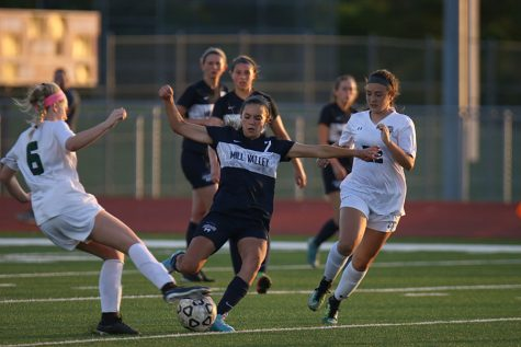 Dribbling the ball, freshman Peyton Wagoner passes her opponents on Tuesday, May 22. The girls beat the De Soto Wildcats 2-1 and will play in Topeka on Friday and Saturday for the state title.