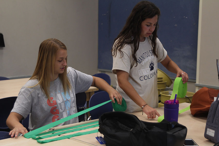 Senior Adelle Warford and junior Cristina Talavera work on cutting streamers for Homecoming week decorations.