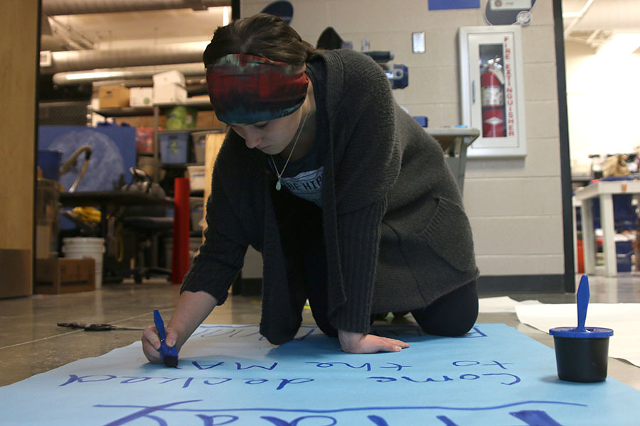 "After coming in for a StuCo workday on Sunday, Jan. 8, student body President Hannah Barnes paints a sign for the winter homecoming dance. ""Creating diverse event opportunities will help get all areas of the school involved,"" Barnes said."