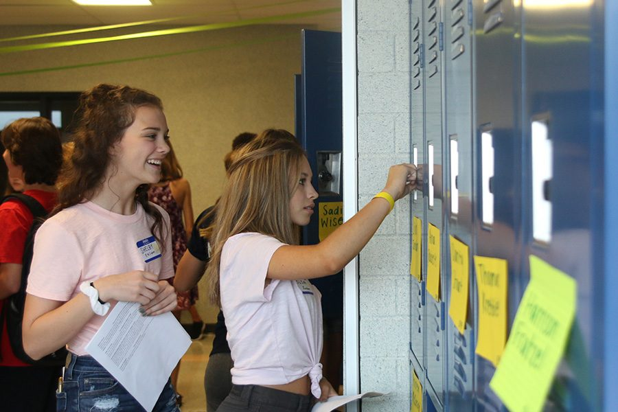 Laughing in the hallway, freshman Shelby Easum helps her friend open her locker for the first time.