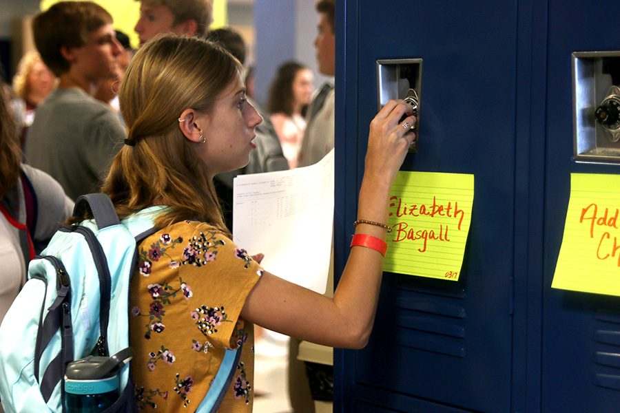 Holding up her schedule, freshman Elizabeth Basgall opens her locker.