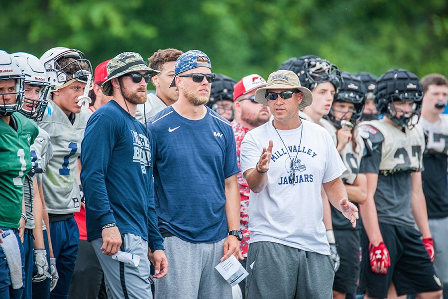With players standing behind them, football coaches Kody Cook, Zack McFall and head coach Joel Applebee watch the football team as they participate at the Blue Springs South football camp on Thursday, June 7.