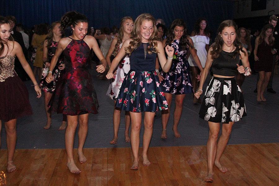 Freshman Quincy Hubert, juniors Jenna Walker and Morgan Koca dance along to a choreographed dance.