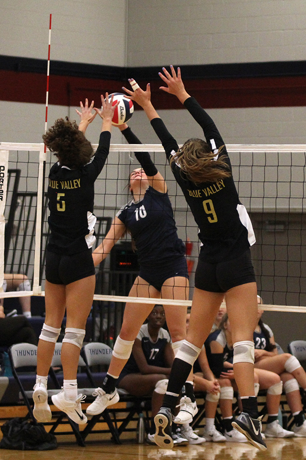 Sophomore+Molly+Carr+hits+against+two+blockers+from+Blue+Valley.
