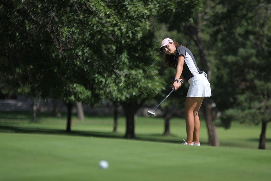 Standing+on+the+green%2C+senior+Sarah+Lawson+uses+her+putter+to+hit+the+ball.