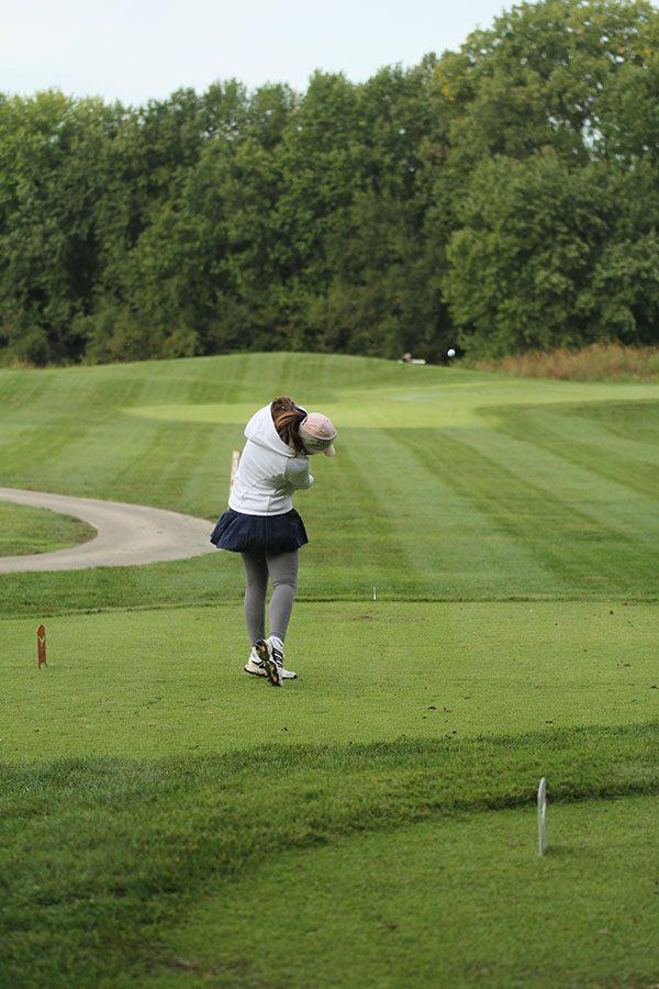 At the fourth tee, freshman Libby Green drives the ball down the fairway.