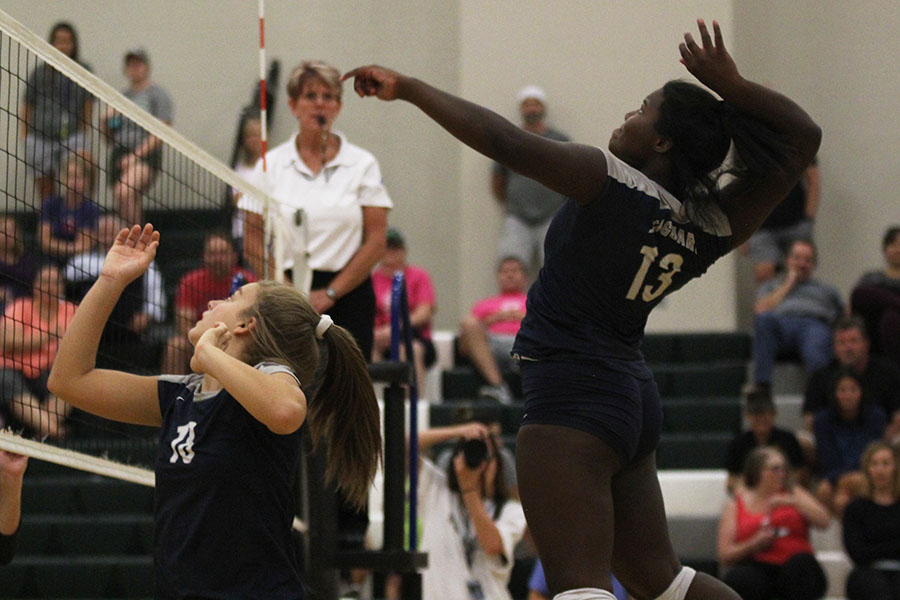 About+to+hit+the+ball+over+the+net%2C+freshman+Taylor+Roberts+jumps+high+into+the+air.