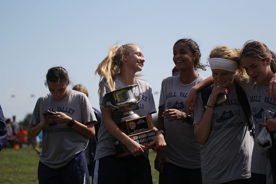 Concluding+the+awards+ceremony%2C+sophomores+Josie+Taylor+and+Madison+Page+smile+with+the+first+place+trophy+in+their+possession+on+Saturday%2C+Sept.+29+at+the+Rey-Pec+cross+country+course.+%22The+team+works+together+by+backing+it+up%2C%22+Taylor+said.+%22Every+single+person+matters+on+the+team+whether+you+come+in+first+for+our+team+or+10th.%22