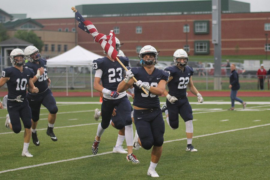 Running out onto the field, senior Trevor Wieschhaus waves the American flag.