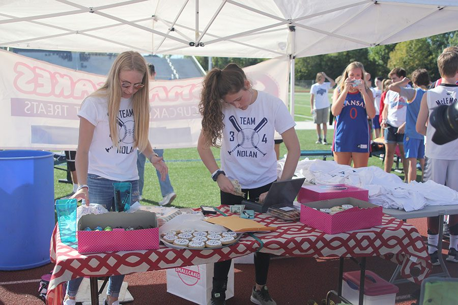 Under the fundraising tent, senior Lexi Ballard and junior Brynn Ayers help register teams and sell Team Nolan gear.