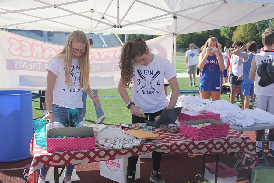 Under the fundraising tent, senior Lexi Ballard and junior Brynn Ayers help register teams and sell Team Nolan gear.