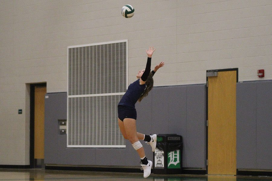 While in the air, sophomore Anna Judd serves the ball, at DeSoto High School on Thursday Sept. 20.