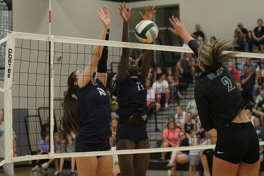 Blocking+a+hit+from+DHS%2C+sophomore+Molly+Carr+and+junior+Faith+Archibong+reach+their+hands+above+the+net.