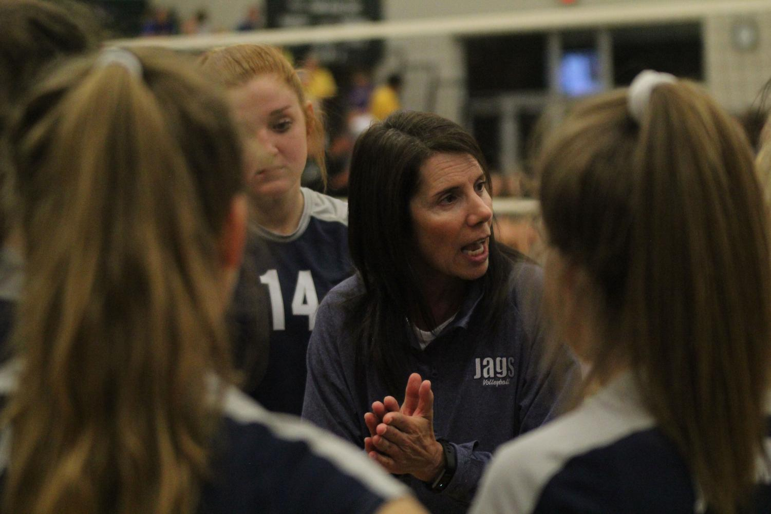 In+between+set+two+and+three%2C+head+coach+Debbie+Fay+talks+with+the+players+in+a+huddle.%0A