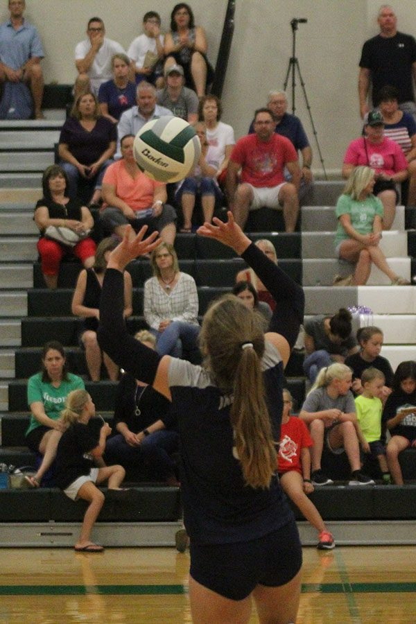 Raising two hands above her head, sophomore Anna Judd sets up a ball for her teammate.