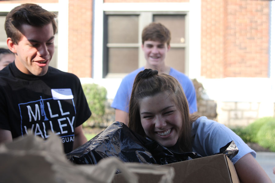 Picking up a large box full of school supplies, senior Annie Myers drops off supplies donated to a Youth for Refugees school supplies drive at Kansas City International Academy.