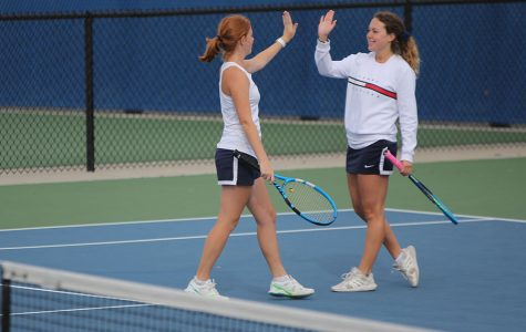Celebrating a good shot, doubles partners Josie Carey and Sydney Fisher high five while trading positions on the court.