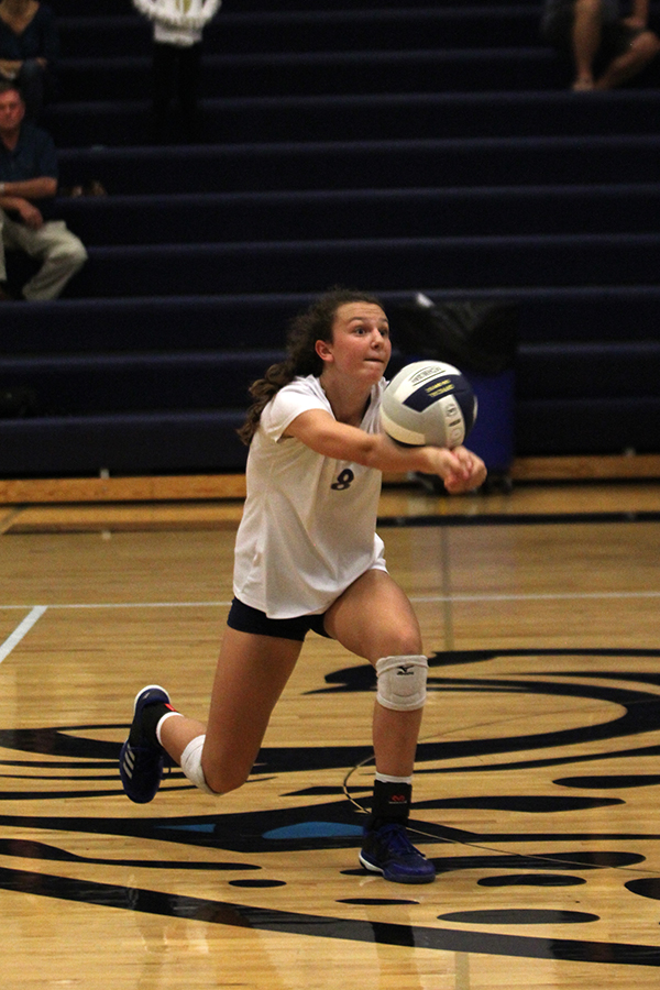 Reaching+for+the+ball%2C+freshman+Amara+Traiger+digs+in+order+to+get+the+ball+over.+