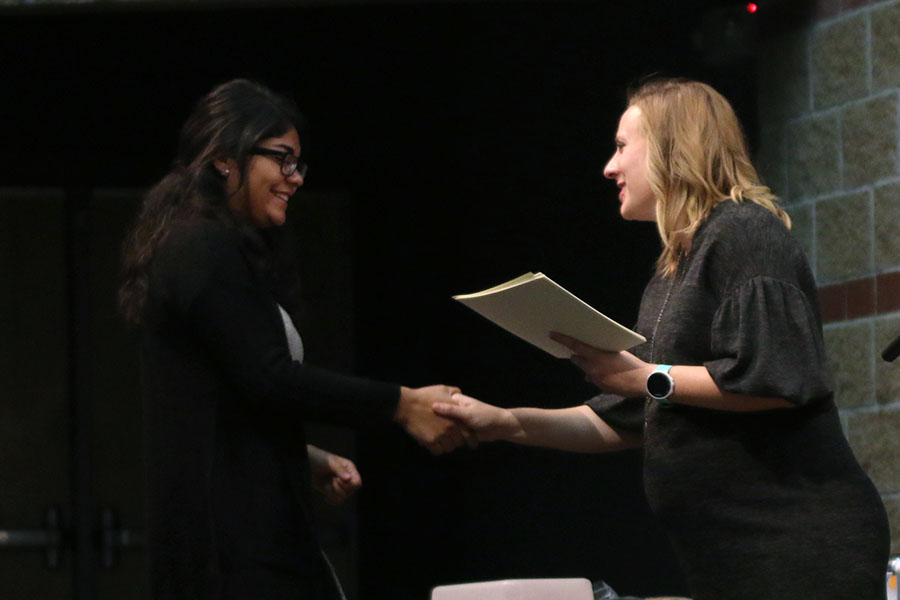 Shaking English teacher Page Anderson's hand, senior Fatima Hernandez is inducted into National English Honors Society on Wednesday, Oct. 10 in the Little Theater.