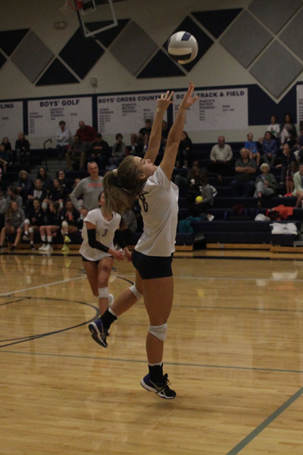 Jumping+to+the+other+side+of+the+court%2C+junior+Whitney+Van+Dyke+sets+the+ball+for+the+hitter.