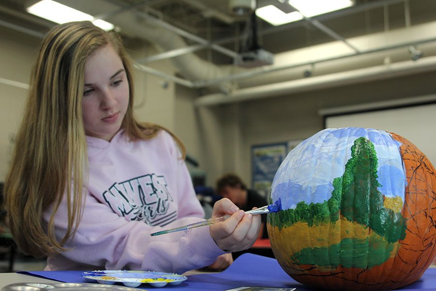 On+Wednesday%2C+Oct.+31+art+teacher+Jodi+Ellis%27+drawing+students+replicate+famous+paintings+onto+pumpkins%2C+for+a+fun+and+festive+twist.+Painting+a+pumpkin%2C+sophomore+Courtney+Zymball+recreates+%22Wheat+Field+with+Cypresses%22+by+Vincent+Van+Gogh.+