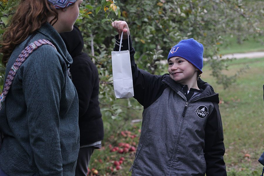 Holding up his bag, sophomore Charlie Peterson shows senior Makayla King his newly picked fruit.
