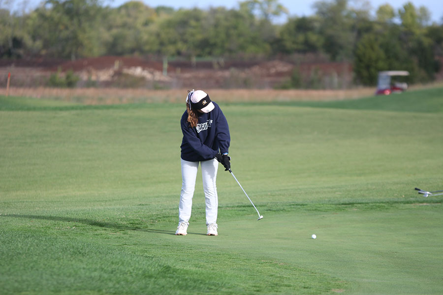 With+her+eye+on+the+ball%2C+senior+Sarah+Lawson+uses+her+putter+on+the+green.