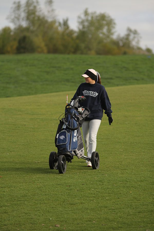Walking down the fairway, senior Sarah Lawson chats with the other two golfers in her tournament group.