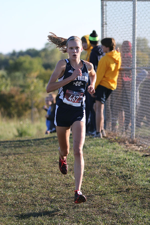 Picking+up+her+pace%2C+freshman+Katie+Schwartzkopf+sprints+down+the+straight+away+to+catch+up+to+her+first+place+opponent.+