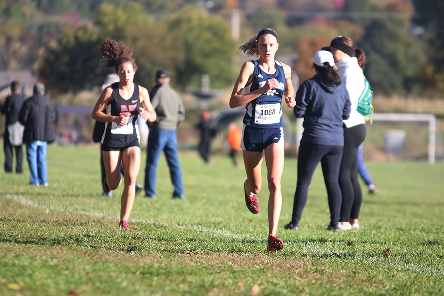 At+the+halfway+mark+of+the+course%2C+freshman+Katie+Schwartzkopf+picks+up+her+pace+to+maintain+her+first+place.+