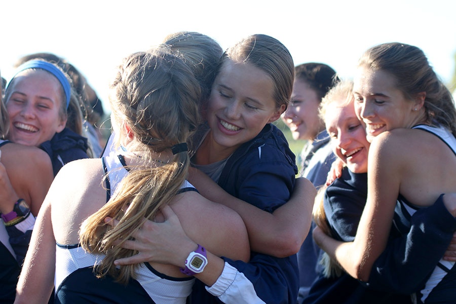 Walking+up+the+field+after+their+race%2C+teammates+that+came+to+support+run+up+to+hug+and+congratulate+the+girls.+