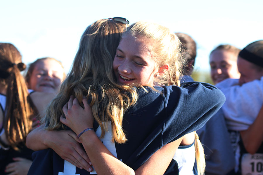After+the+race%2C+sophomore+Josie+Taylor+smiles+as+senior+Caroline+Rutledge+embraces+her.++