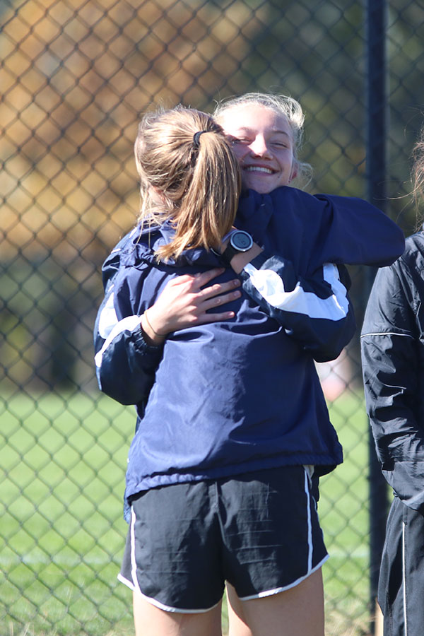 As+junior+Molly+Haymaker+goes+up+to+receive+her+medal%2C+she+hugs+sophomore+Josie+Taylor+on+the+way.+Haymaker+placed+fourth.+