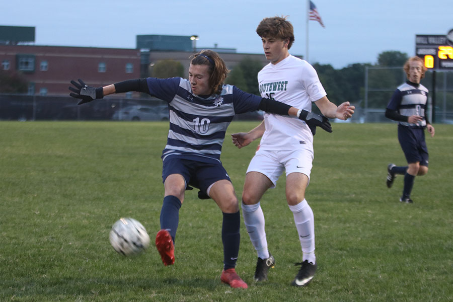 Defending+the+ball%2C+sophomore+Quinten+Blair+kicks+it+away+for+the+BVSW+player.+