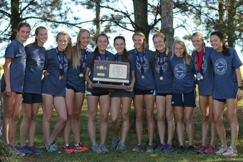 "After placing first at state for the first time in school history, the girls cross country team holds up their championship trophy at Rim Rock Farm on Saturday, Oct. 27. ""Sometimes you just have to expect for something to happen in order to achieve it,"" senior Delaney Kemp said about their results."
