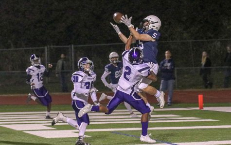 "As a Topeka West player puts his hand into senior Logan Talley's face, Talley tries to catch the ball on Friday, Oct. 26.  ""[The touchdown] gave us momentum throughout the whole entire game,"" Talley said"