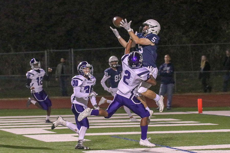 As+a+Topeka+West+player+puts+his+hand+into+senior+Logan+Talley%E2%80%99s+face%2C+Talley+tries+to+catch+the+ball+on+Friday%2C+Oct.+26.++%E2%80%9C%5BThe+touchdown%5D+gave+us+momentum+throughout+the+whole+entire+game%2C%E2%80%9D+Talley+said
