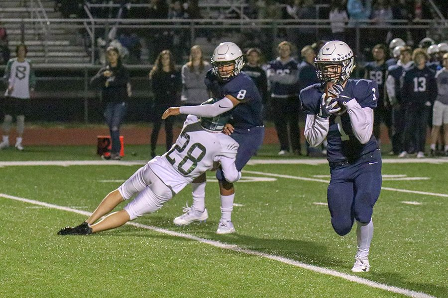 """After being thrown the ball, senior Cameron Young runs the ball downfield against Blue Valley Southwest on Friday, Oct. 19. """"It's the best feeling there is."""" said Young """"There is nothing like playing on Friday night with your brothers by your side."""""""
