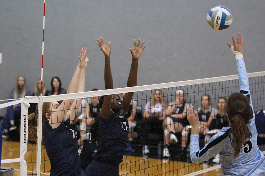 With+their+opponent+reaching+for+the+ball%2C+junior+Faith+Archibong+and+freshman+Brylee+Peterson+jump+to+block+it.