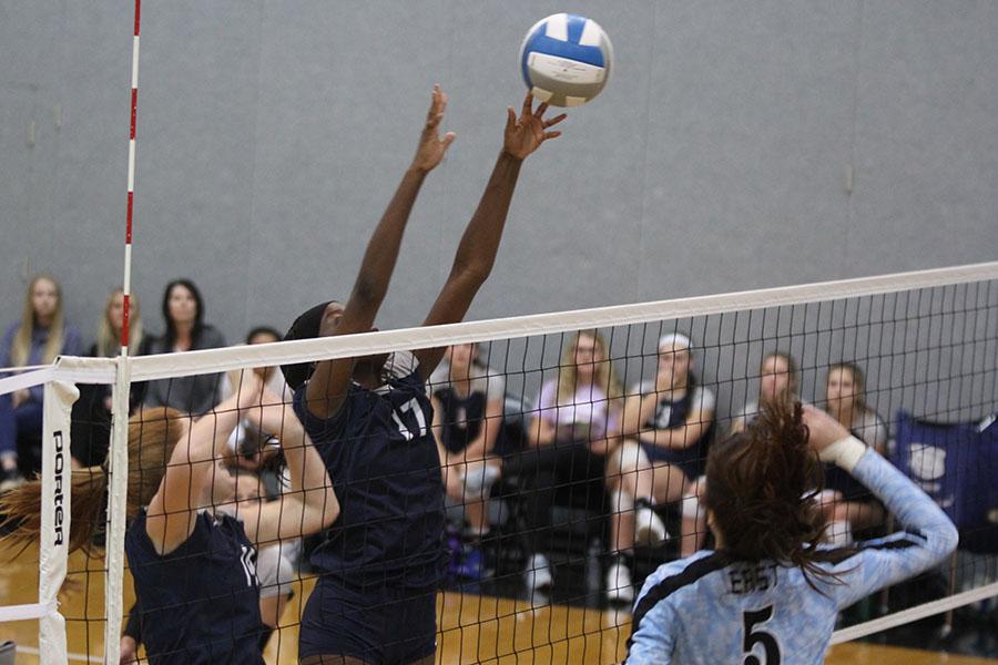 Reaching+over+the+net%2C+junior+Faith+Archibong+blocks+a+ball+that+her+opponent+has+hit.