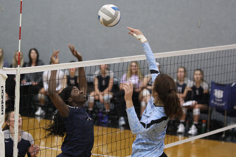 With+her+arms+in+the+air%2C+junior+Faith+Archibong+reaches+over+the+net+to+stop+a+ball+from+coming+over.