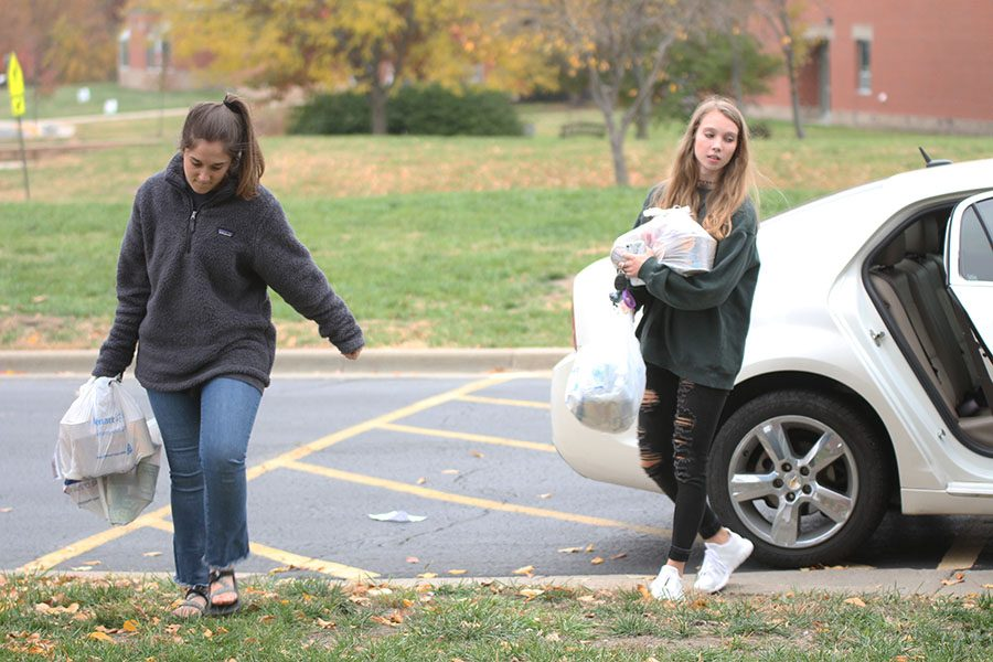 Unloading their car, senior student body president Hannah Barnes and senior student body treasurer Kate Backes bring their donations to the school for pick-up.