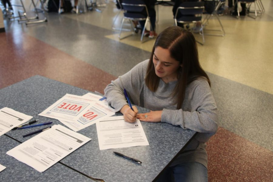 Kneeling down, senior Hannah Barnes finishes filling out her registration form.
