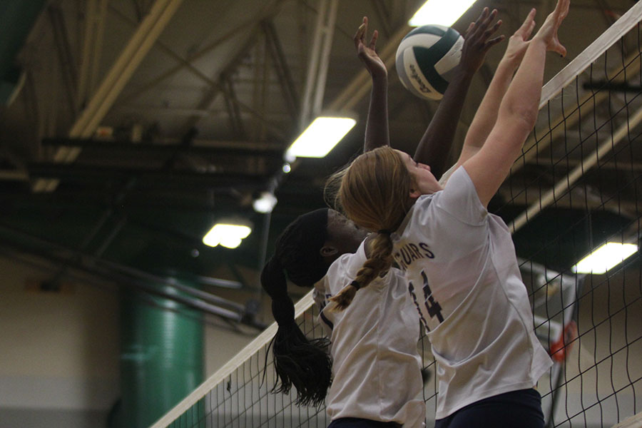Attempting+to+block+the+ball%2C+junior+Faith+Archibong+and+freshman+Brylee+Peterson+jump+and+reach+over+the+net.