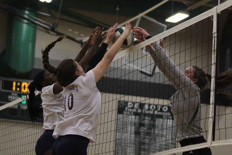 With the ball at the net, junior Faith Archibong and sophomore Molly Carr fight their opponent for possession.