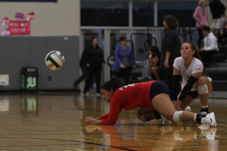While+sliding+on+the+court%2C+senior+Sydney+Pullen+performs+a+dig.