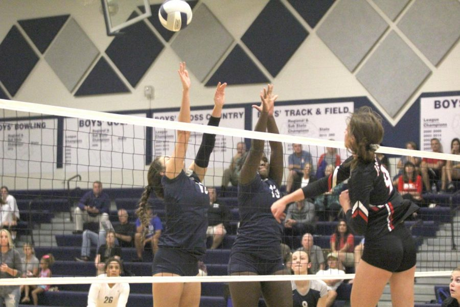 With the opponent trying to block the hit, sophomore Molly Carr, attempts to score a heavily contested point against 6A opponent Blue Valley West on Tuesday, Sept. 11.