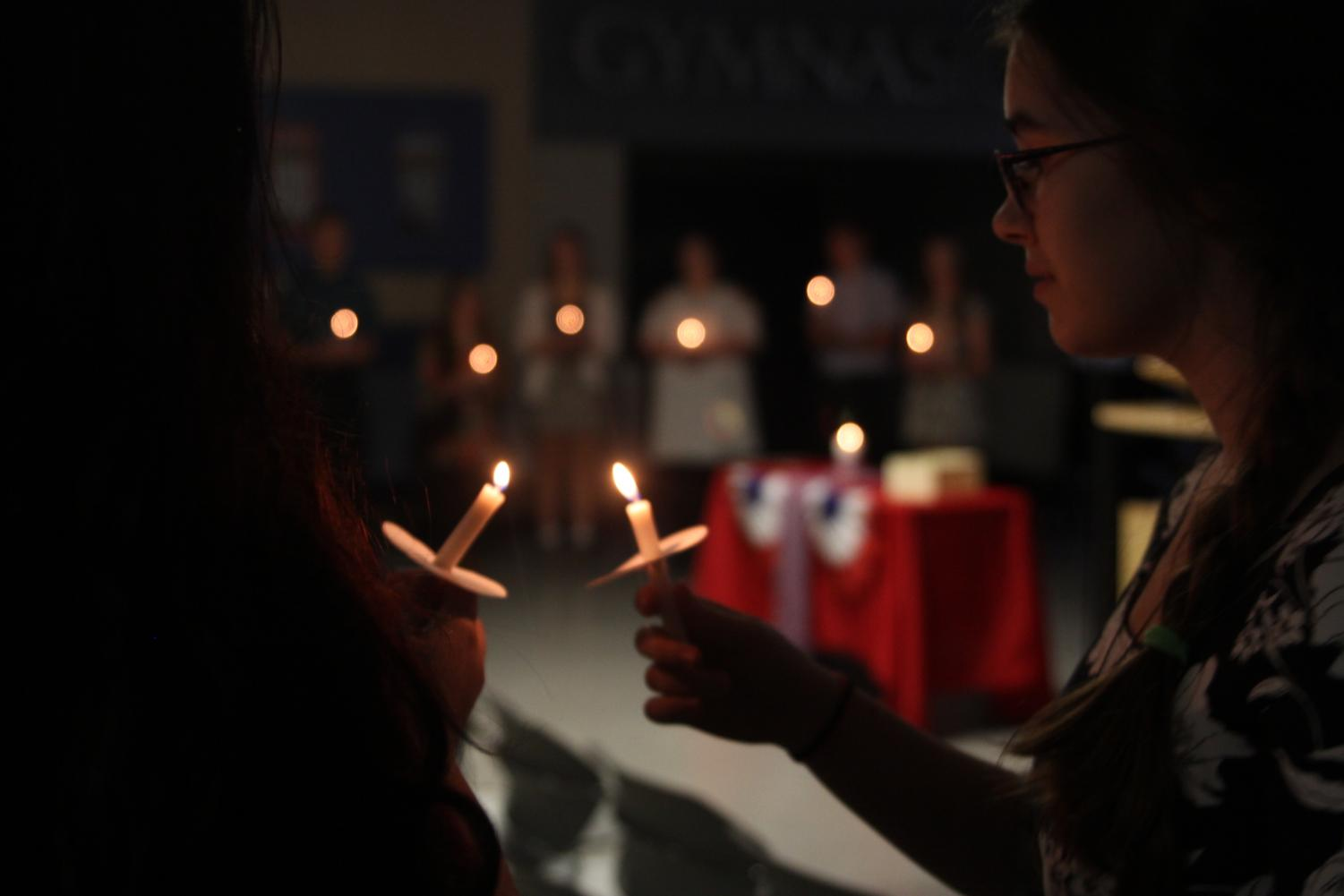 "During the French National Honors Society induction ceremony on Thursday, Oct. 4, junior Joan Downey lights the candle of the person next to her. ""I love the sound of French. I love French culture. I love reading books in French."""
